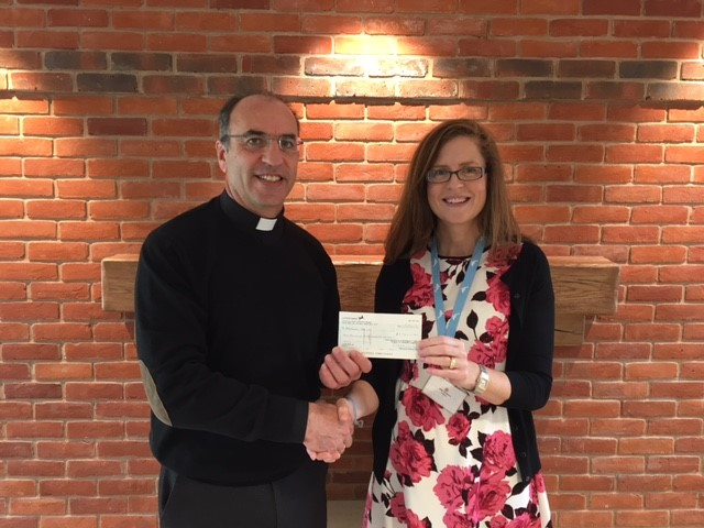 Fr Pepe presents cheque to Alexander Devine Hospice